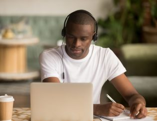 man wearing headphones watching webinar making notes study online