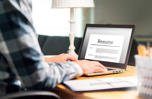 Man writing resume and CV in home office with laptop. Applicant