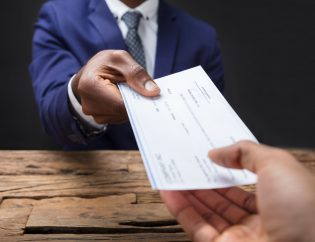 Businessman Giving Cheque To His Colleague