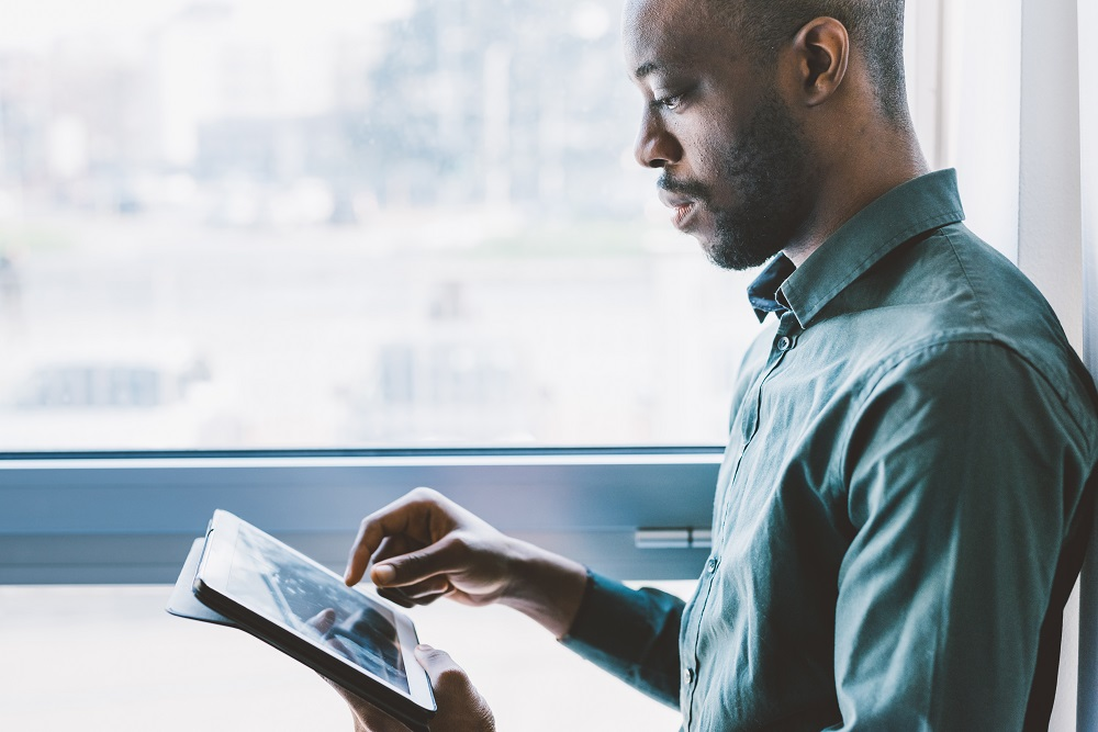 Half length of young handsome afro businessman near a window holding a tablet, looking down and tapping the screen - business, working, job concept