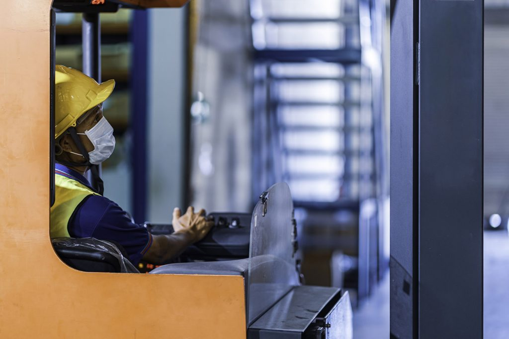Asian foreman in uniform with helmet and protective face mask drive forklift in warehouse cargo with copy space. Concept of new normal work in logistic industry, factory after Covid 19 pandemic
