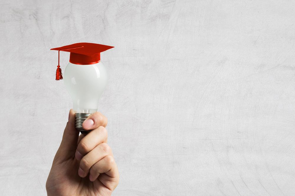 Lightbulb with graduation cap on