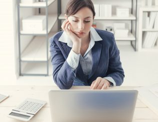 Depressed bored businesswoman working at office desk and networking with a laptop, boring job concept